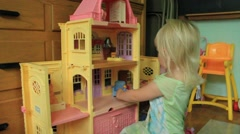 Two year old plays dollhouse Stock Footage