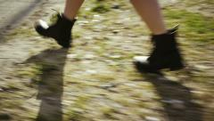 Woman wearing black boots walking Stock Footage