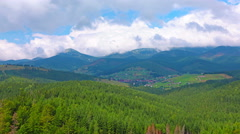 Mountain village in a forest and cloudy sky. 4K. FULL HD, 4096x2304. Stock Footage