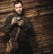 handsome man wearing cardigan with vintage camera in wooden house interior - stock photo