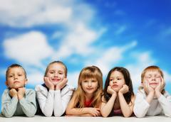 group of little children lying in a row against blue sky - stock photo