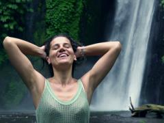 Happy woman feeling free next to the waterfall, slow motion shot at 240fps Stock Footage