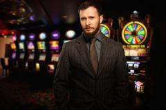 handsome well-dressed man against slot machines in a casino - stock photo