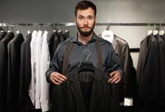 Handsome man with beard choosing jacket in a shop Stock Photos