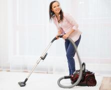 Young cheerful brunette woman vacuum cleaning carpet in home interior Stock Photos