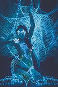 beautiful woman with body art glowing in ultraviolet light and freezelight ba - stock photo