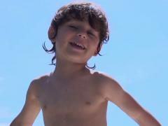 Boy waving hands and smiling to the camera, slow motion shot at 240fps Stock Footage