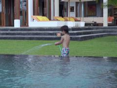 Boy playing with hose in the garden, slow motion shot Stock Footage