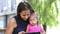 Young mother with baby in the park playing on the laptop. Stock Footage
