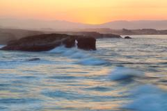 Beautiful sunset and stone arches on playa de las catedrales during inflow, s Stock Photos