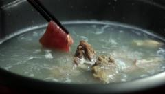 Sliced pork shabu-shabu put to boiling water pot. - stock footage
