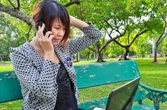 A stressed woman talk mobile phone with laptop in nature Stock Photos