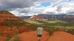 Man Standing On High Bluff Admires Eastern Sedona View Stock Footage