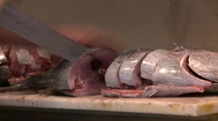 A butcher cuts fresh fish in a market. Stock Footage