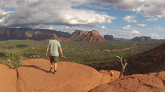 Man Walks To Edge Of Bluff And Admires Sedona View - stock footage