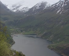 Scenic overlook of Geiranger town and cruise terminal + pan Geirangerfjord Stock Footage
