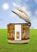 old rice cooker with nice garden and sky background - stock photo