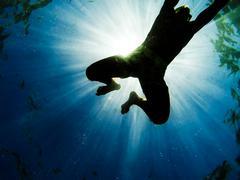 man swimming in the sea with sunbeams shining through - stock photo