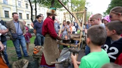 Blacksmith teach children medieval tradition of making armor and swords Stock Footage