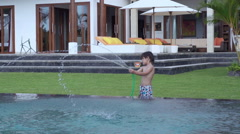 Boy playing with hose in the garden, slow motion shot at 240fps Stock Footage