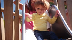 Mother and Son Go Down Slide Stock Footage
