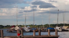Dock on lake w/Sailboats as spring storm clouds build Time-lapse  Stock Footage