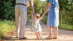 Baby granddaughter walking with her grandparents outdoors Stock Photos