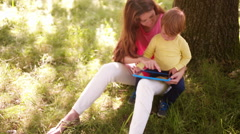 Mother and child enjoying free time in park with tablet Stock Footage