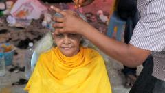 Old woman having hair shaved off at Batu Caves during Thaipusam Hindu festival Stock Footage