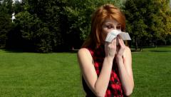 Young attractive woman is in the park - woman blowing her nose with handkerchief Stock Footage