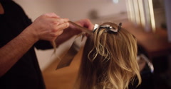 Hairdresser prepares foil highlights on woman's hair - stock footage