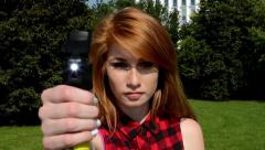 Young attractive woman in the park - woman holds a pepper spray - tree, grass Stock Footage