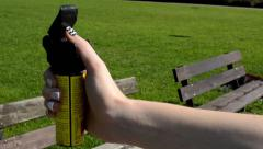 Woman in the park - woman holds a pepper spray - grass in the background - natur Stock Footage