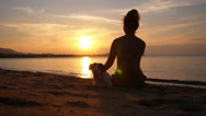 Stock Video Footage of Silhouette of a Young Woman with Dog at Sunrise. Slow Motion.