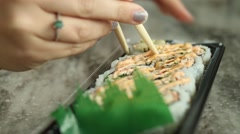 Woman using chop sticks to pick up piece of sushi Stock Footage