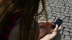 Young attractive woman sits on bech in the park - woman works on the smartphone Stock Footage