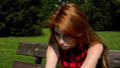Young attractive woman sits on bech in the park - woman is sad (lonely) - nature Stock Footage
