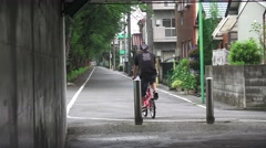 Japanese Bicycle Ride Exits Tunnel Near Tokyo Houses 4K Stock Footage