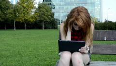 Young attractive woman sits on bech in the park - look into a tablet - modern Stock Footage