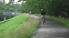Japanese Bicycle Ride On Bike Path Next To Green Hill 4K Stock Footage