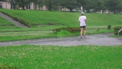 Japanese Jogger On Trail Next To Tama River On Rainy Day 01 4K Stock Footage