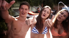 Friends Showing Thumbs Up At Poolside Stock Footage