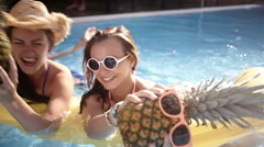 Girls having a silly time with pineapples in swimming pool Stock Footage