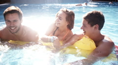 Friends Sharing Lilo in Pool Stock Footage