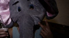 Guy in elephant head showing victory sign to camera Stock Footage
