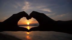 Silhouette Hand in Heart Shape during Sunset. Slow Motion. Stock Footage