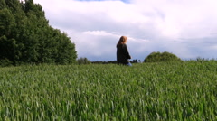 Woman with dark jacket go through wide crop field in summer Stock Footage