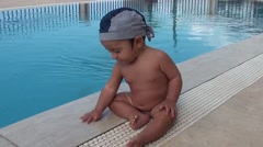 Baby sits at the edge of the swimming pool Stock Footage