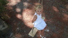 Happy girl in white dress with blond hair on a swing. She is happy and enjoys Stock Footage