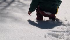 Young child scoops fresh snow with a toy shovel on a bright winter day. Stock Footage